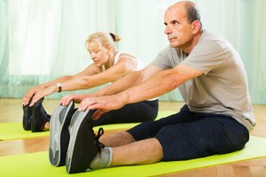 Happy active senior mature spouses warming up muscles before exercising at home